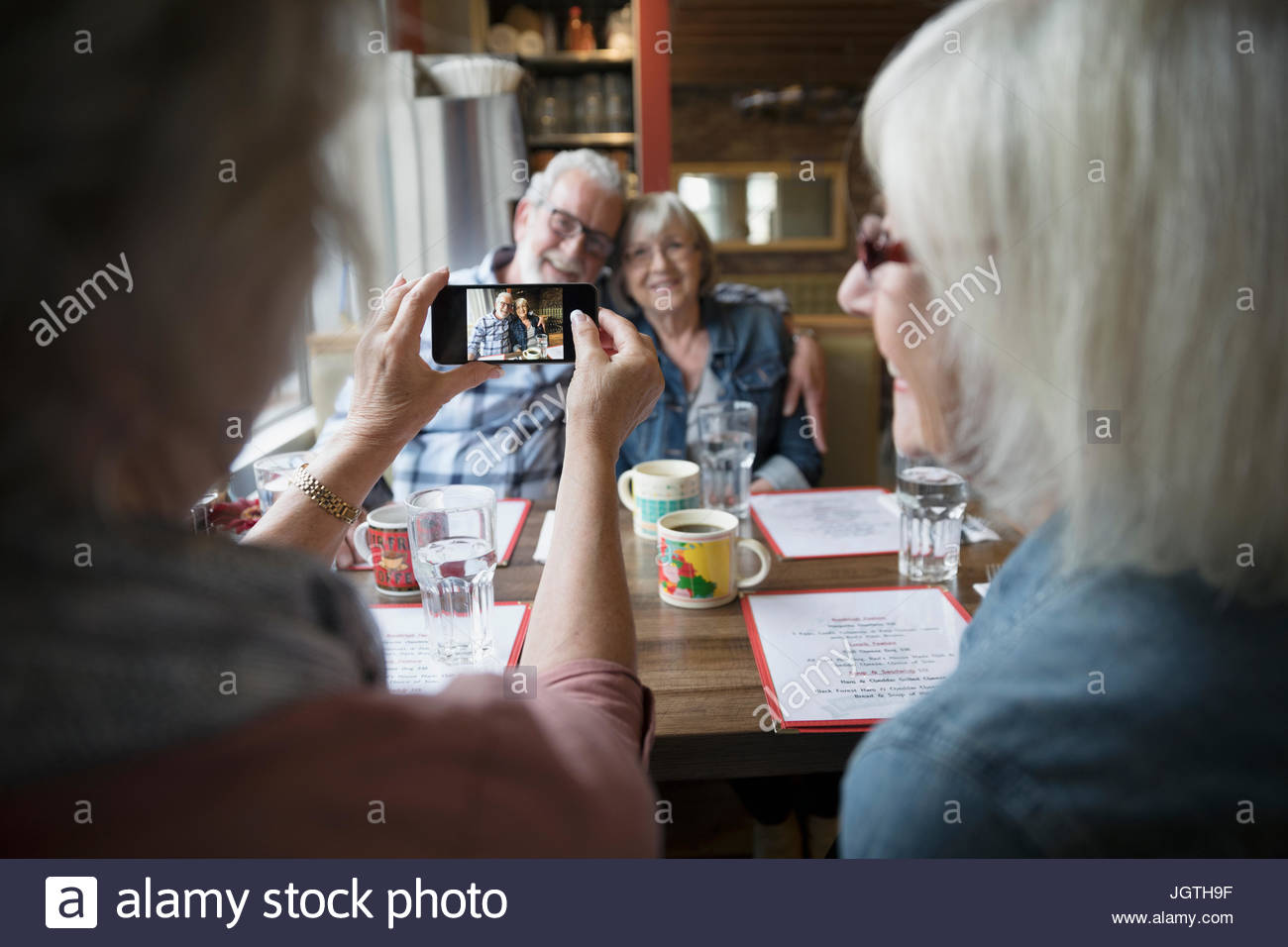 Senior woman photographing senior couple with camera phone in diner booth - Stock Image