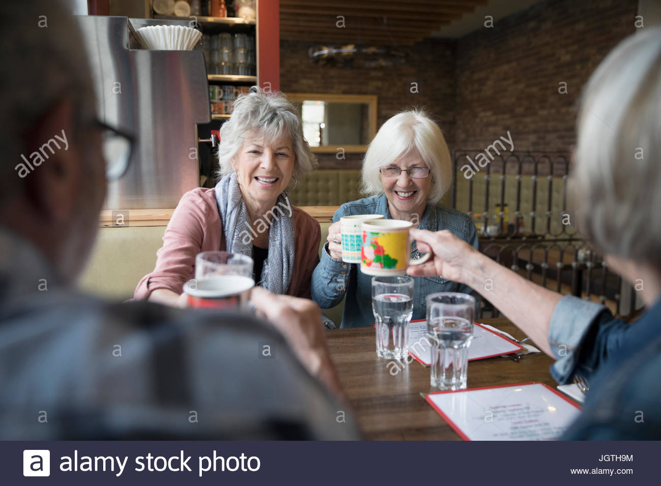 Senior friends toasting coffee mugs in diner booth - Stock Image