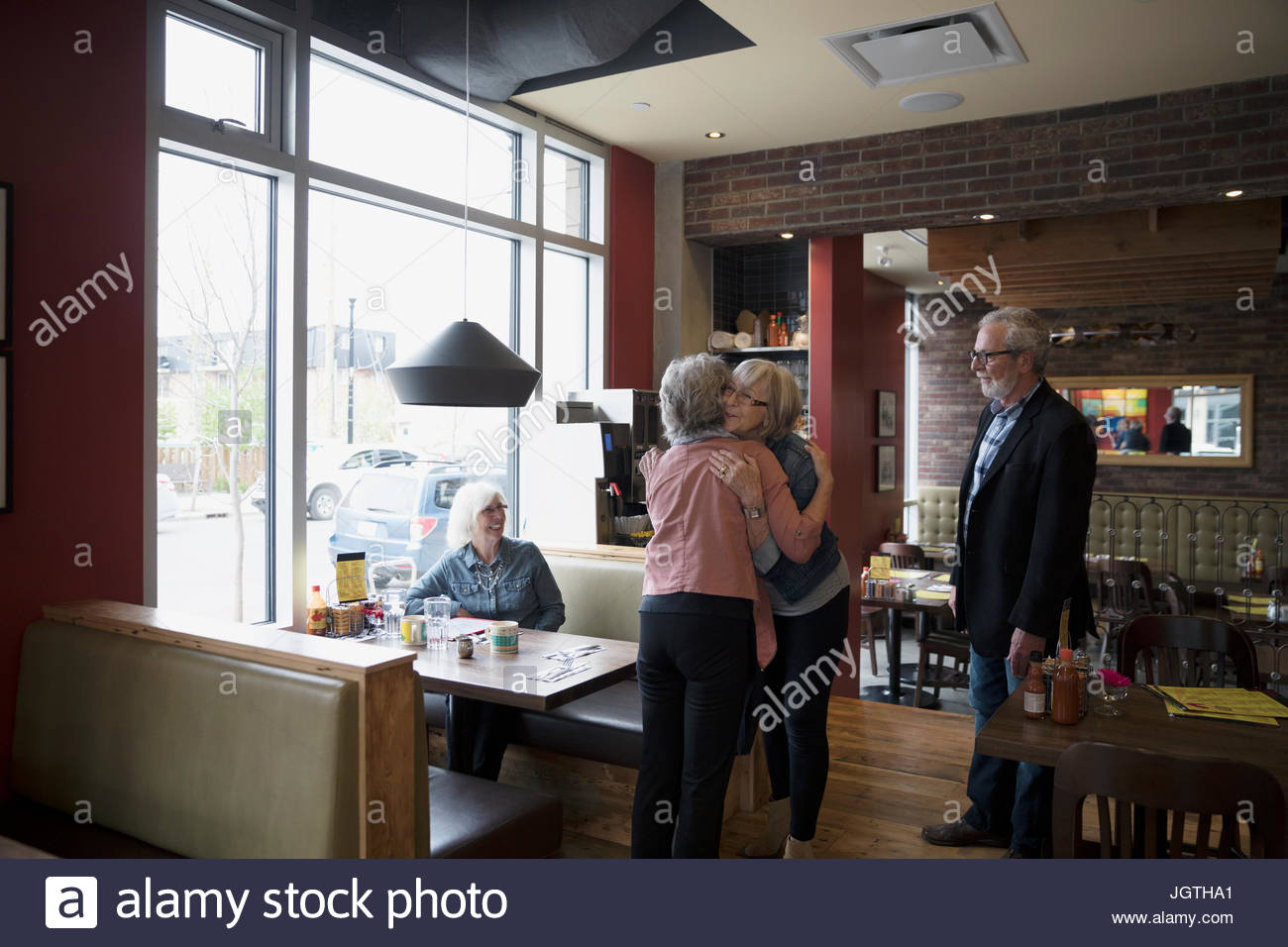 Senior friends greeting, hugging at diner booth - Stock Image