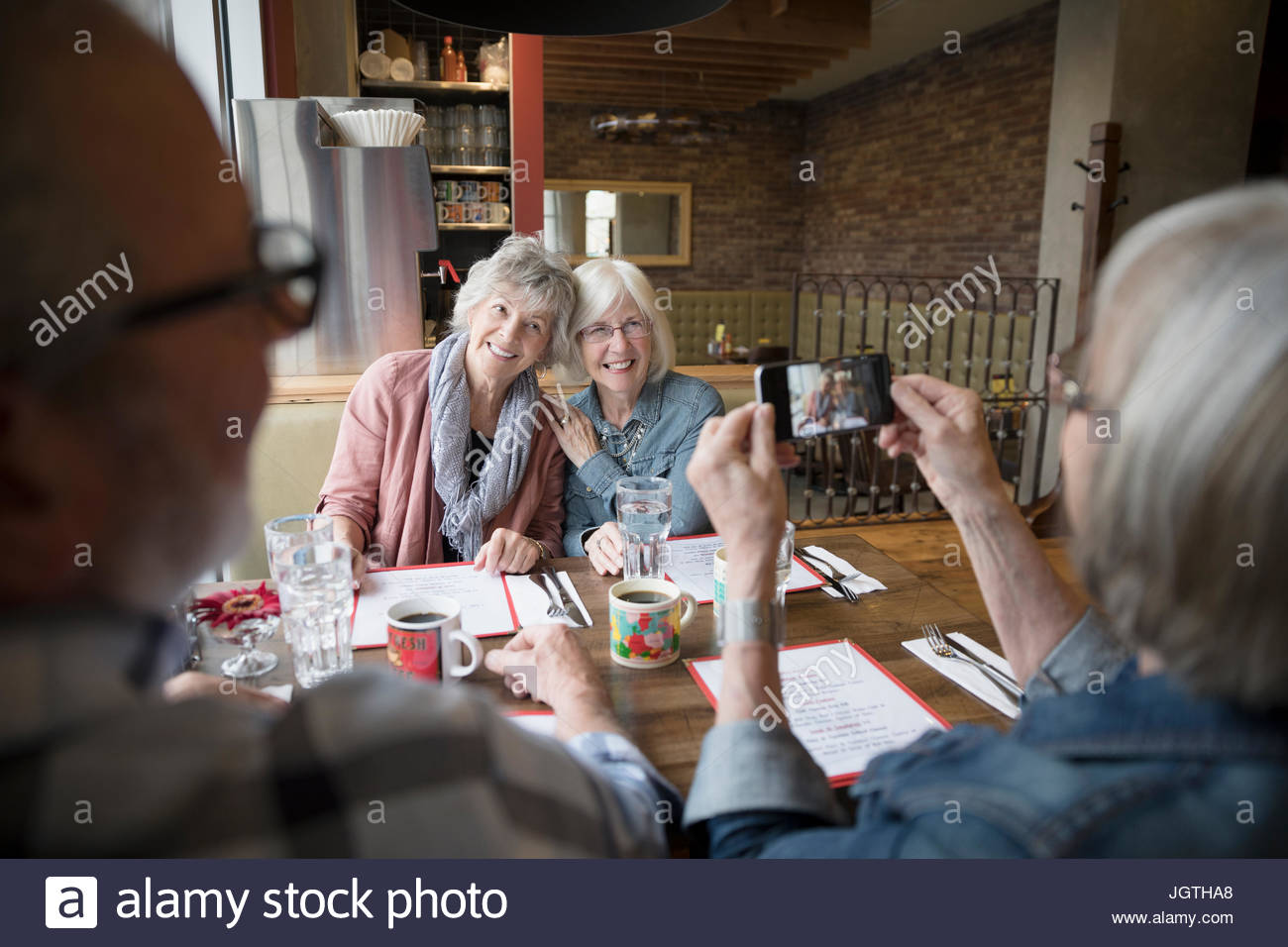 Senior woman photographing friends with camera phone in diner booth - Stock Image