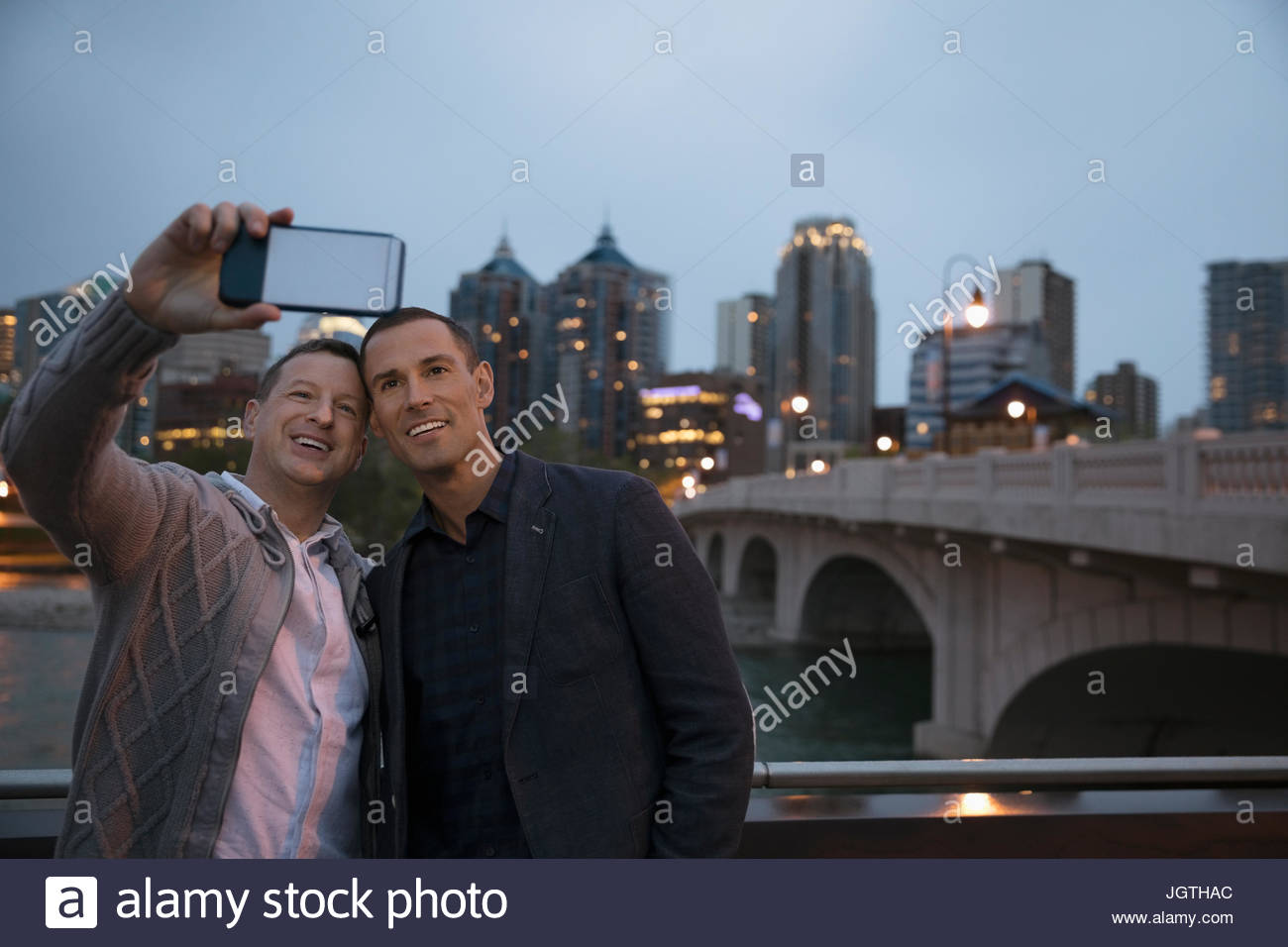 Male gay couple taking selfie with camera phone along urban waterfront at night - Stock Image