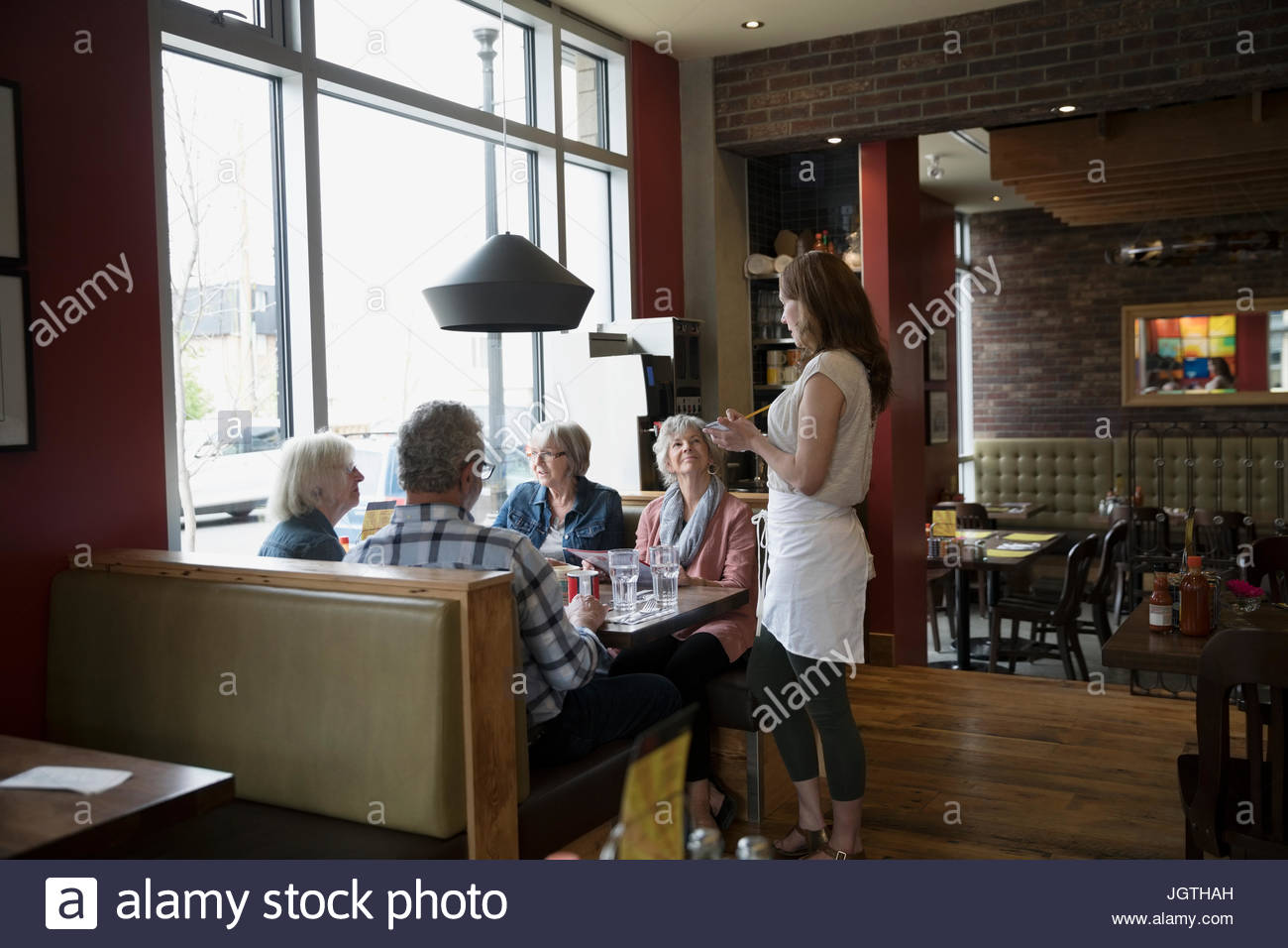 Waitress taking order from senior friends dining in diner booth - Stock Image