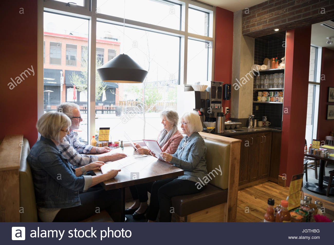 Senior friends dining, looking at menus in diner booth - Stock Image