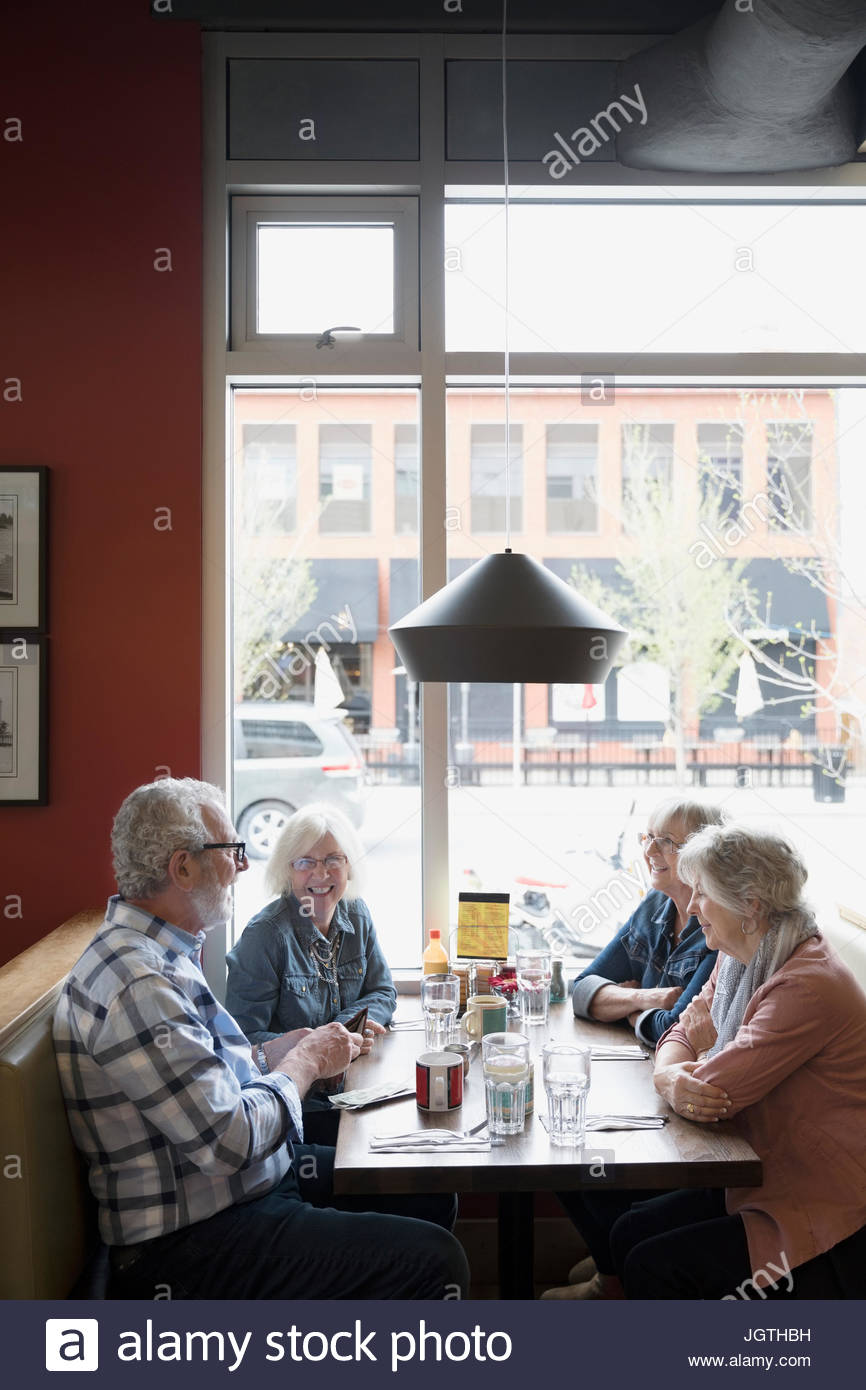 Senior friends dining in diner booth - Stock Image