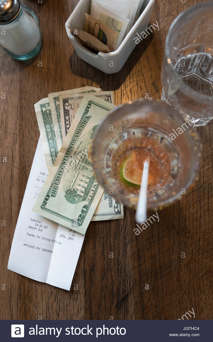 Overhead view restaurant bill and cash change on table - Stock Image