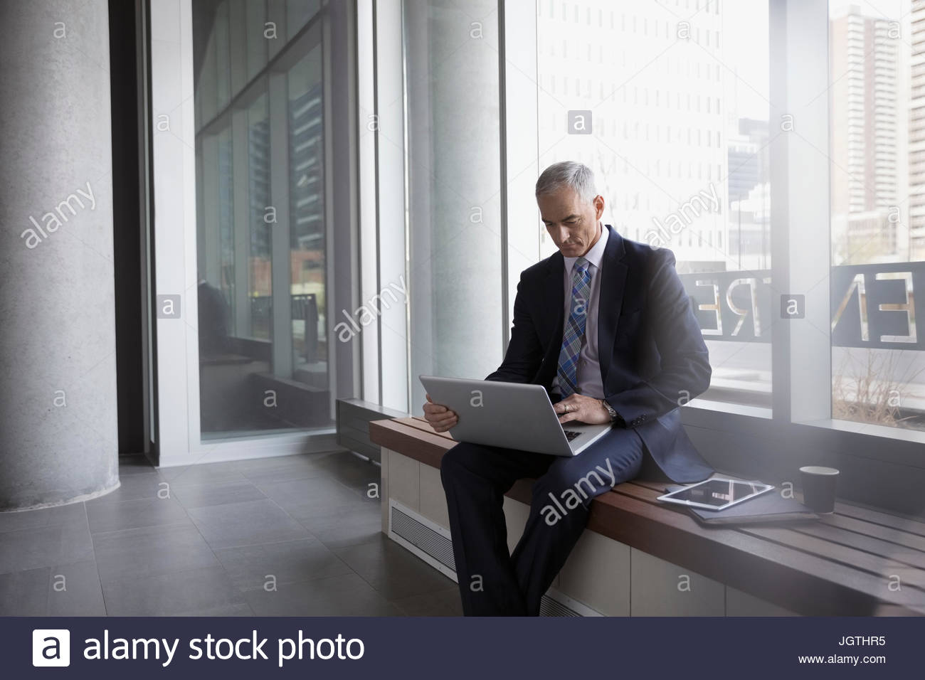 Businessman using laptop on bench in office lobby - Stock Image