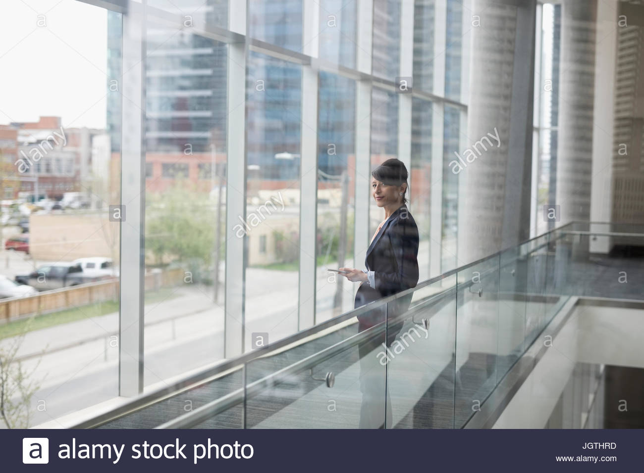 Businesswoman with cell phone at office window - Stock Image