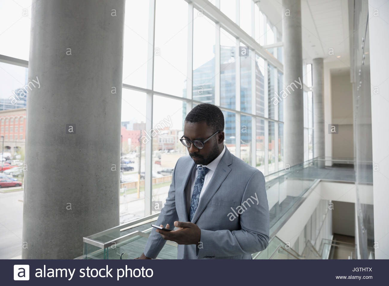 Businessman texting with cell phone in office - Stock Image