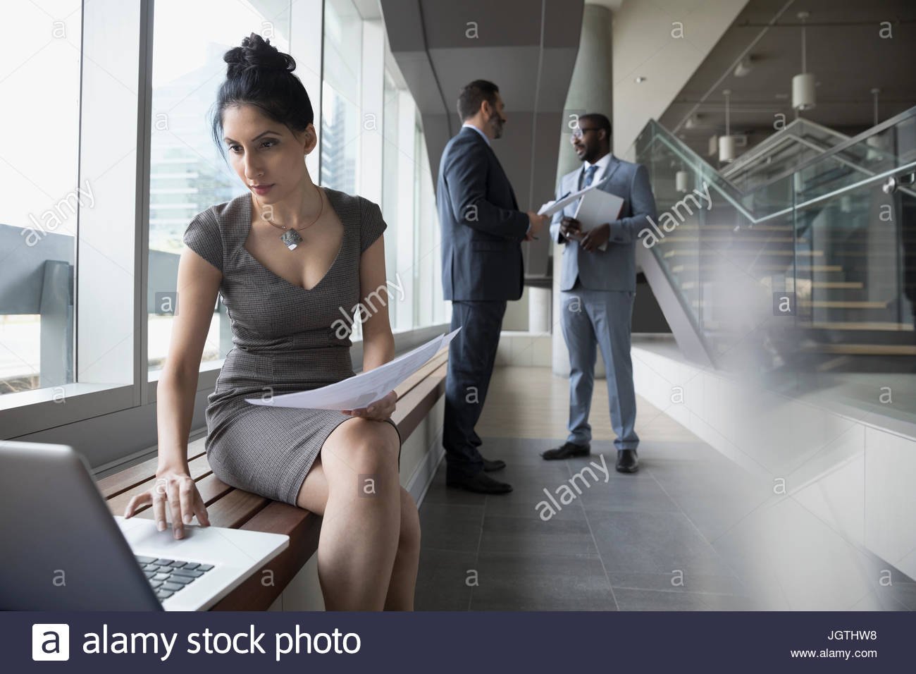 Businesswoman with paperwork working at laptop in office - Stock Image