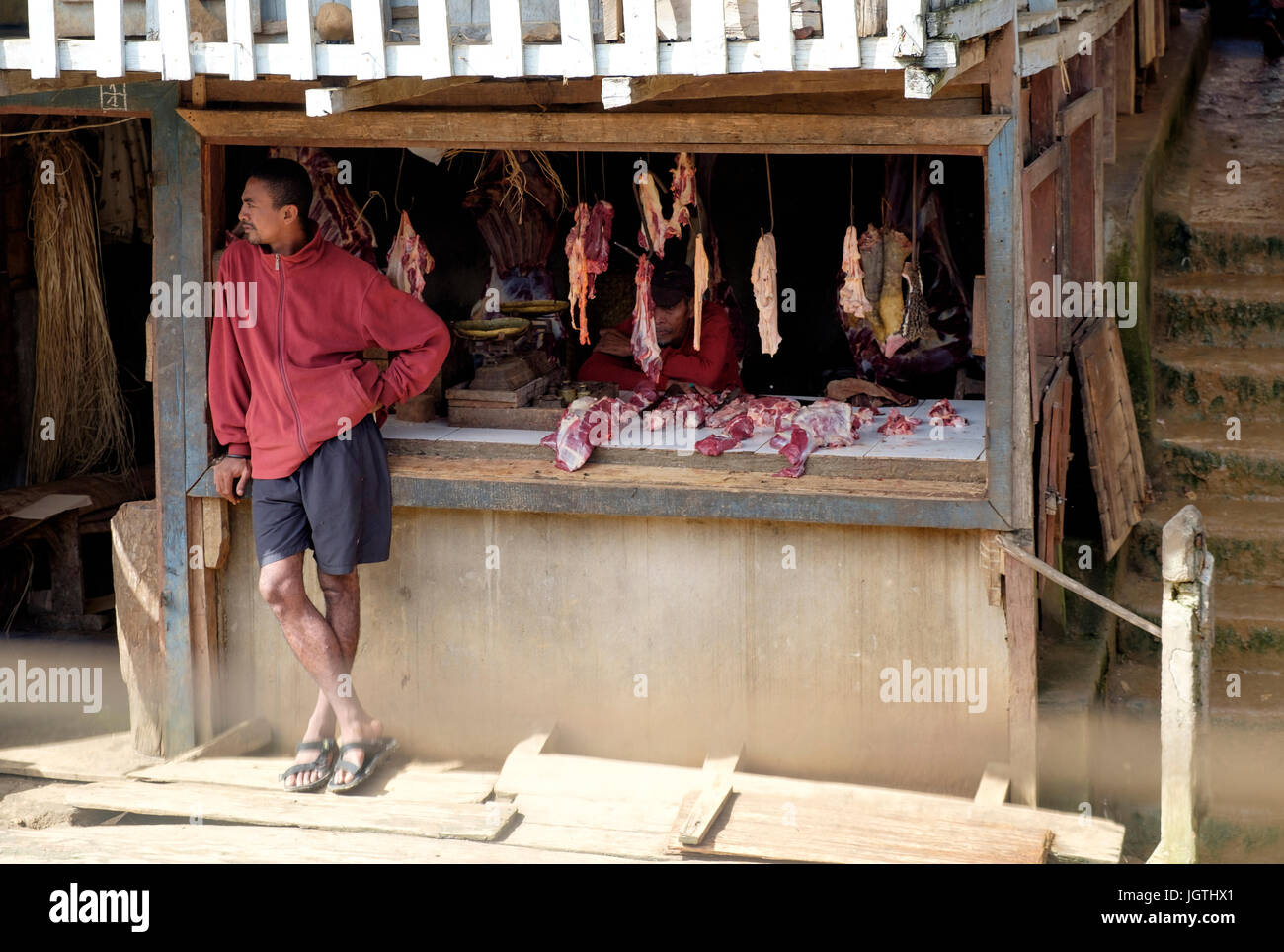 A trackside butcher waits to sell at one of the stations along the Fianarantsoa-Côte Est railway in Madagascar. - Stock Image