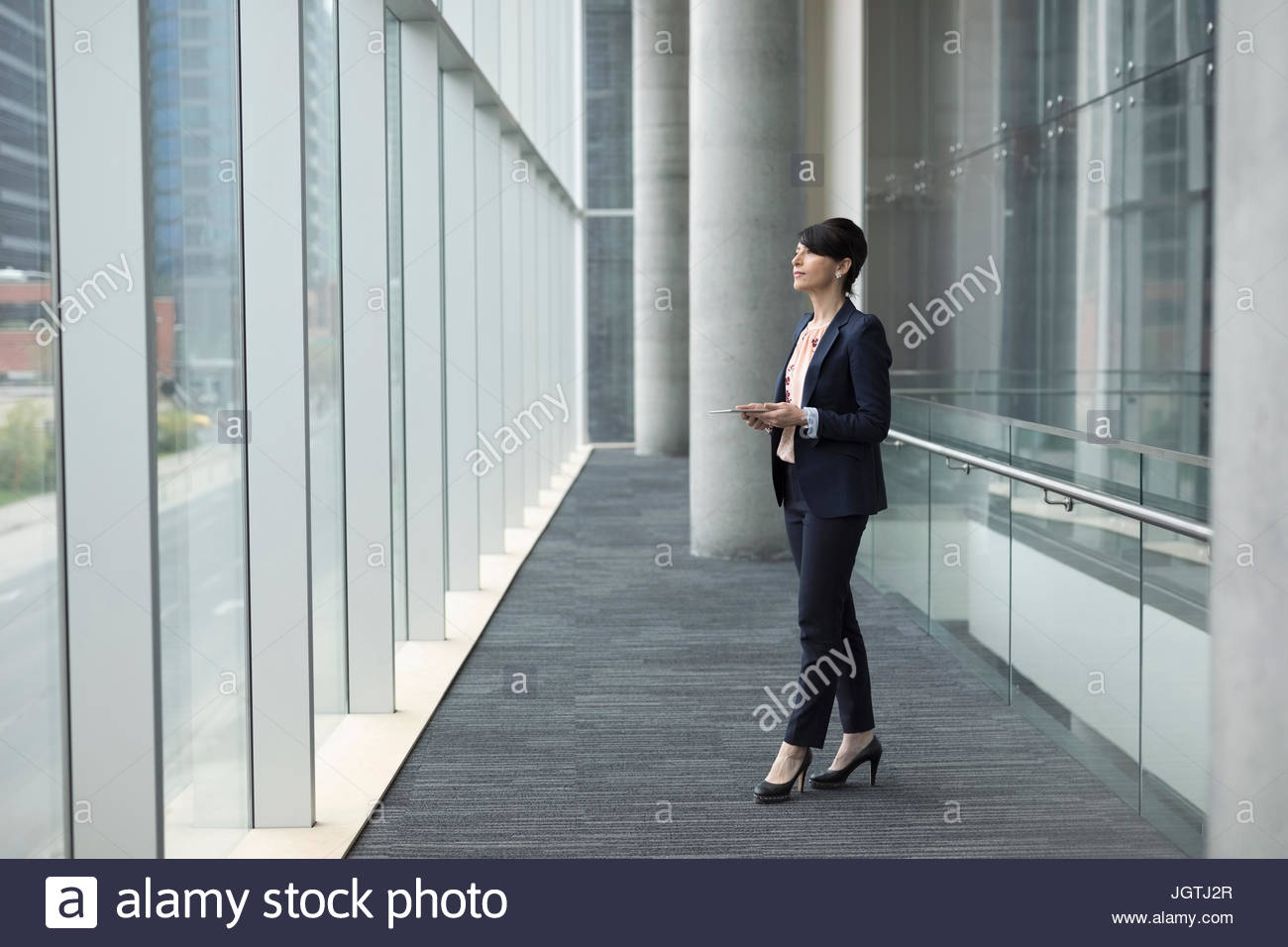 Pensive businesswoman with cell phone looking out office window - Stock Image