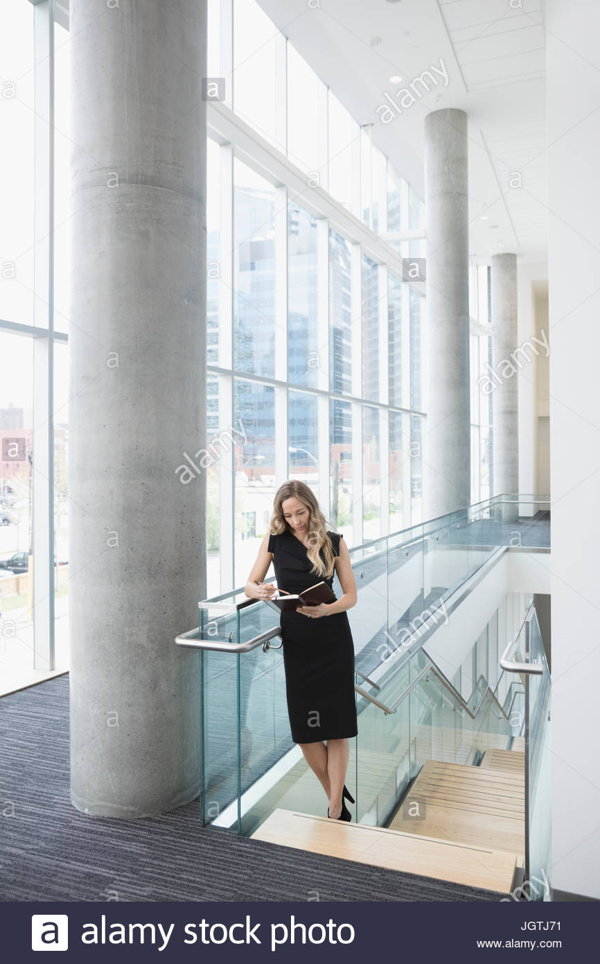 Businesswoman viewing journal schedule at top of office stairs - Stock Image