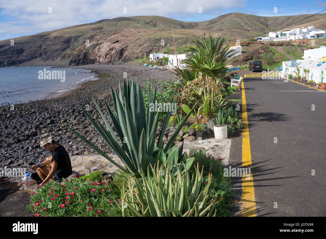 Girl sitting at volcanic pebble beach at the fishing village Playa Quemada, Lanzarote island, Canary islands, Spain, Stock Photo