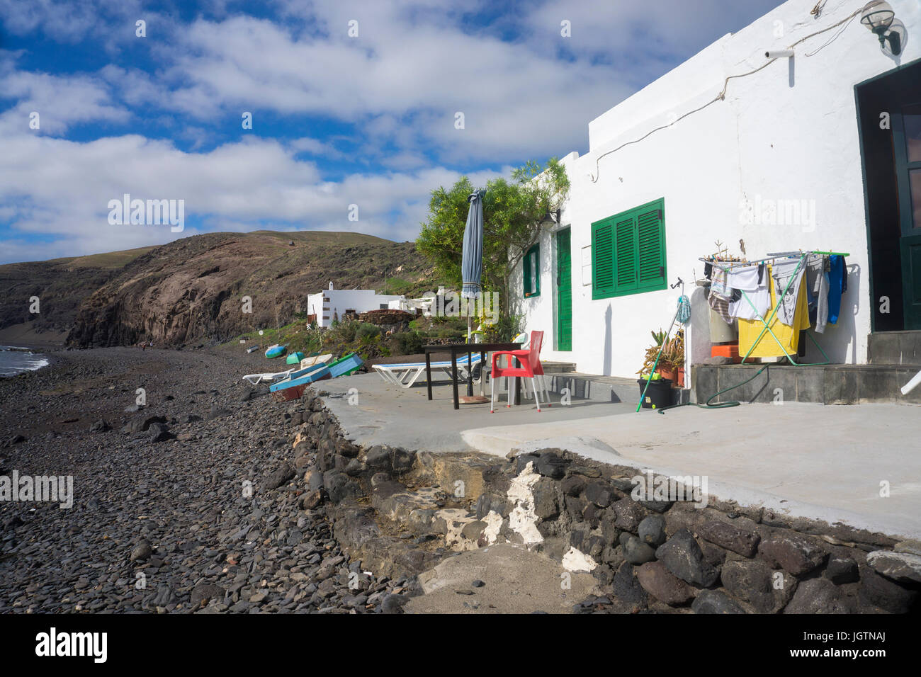 Small fisherman house with out hanging laundry, beach of the fishing village Playa Quemada, Lanzarote island, Canary Stock Photo