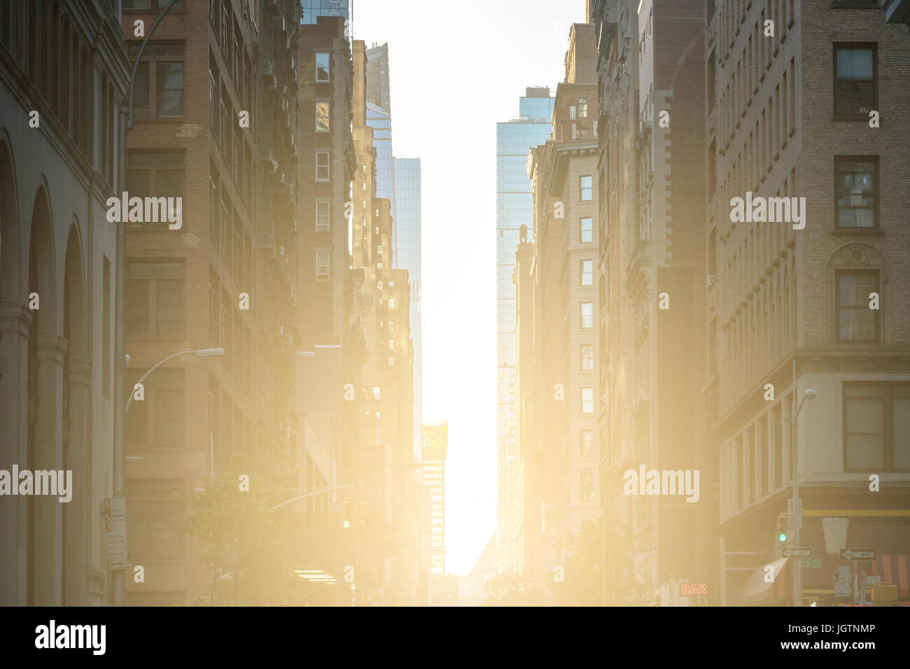 Sunlight shines down the crowded streets of New York City NYC - Stock Image
