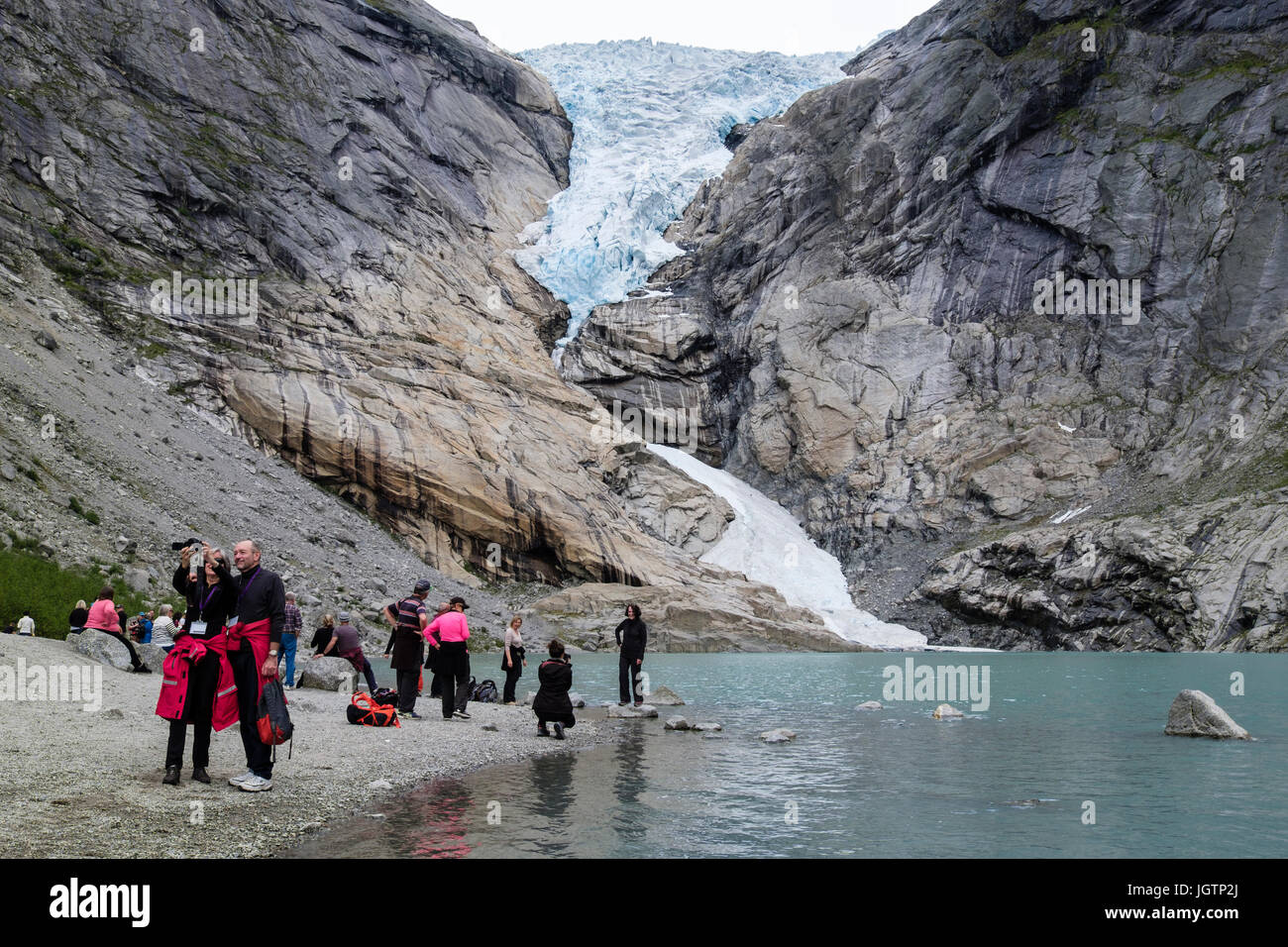 Tourists visiting Briksdalsbreen or Briksdal glacier arm of Jostedalsbreen above Briksdalsbrevatnet lake in Jostedalsbreen National Park, Norway Stock Photo