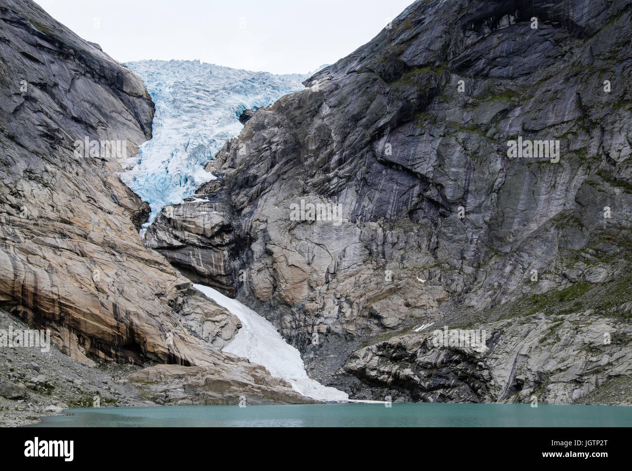 Briksdalsbreen or Briksdal glacier is an arm of Jostedalsbreen glacier above Briksdalsbrevatnet glacial lake in Jostedalsbreen National Park Norway Stock Photo