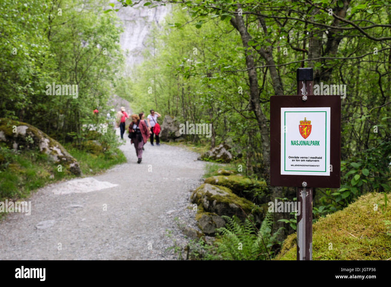 Sign for Jostedalsbreen nasjonalpark or Jostedalsbreen National Park with tourists on Briksdalsbreen glacier trail - Stock Image
