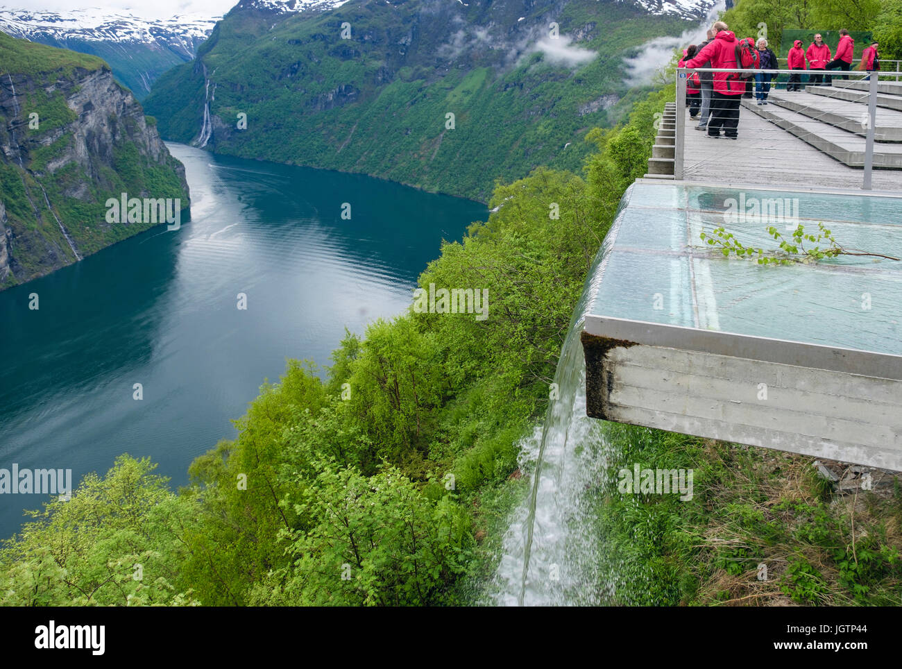 Artificial waterfall with tourists looking at view from high Eagles Road viewpoint platform overlooking Geirangerfjorden - Stock Image