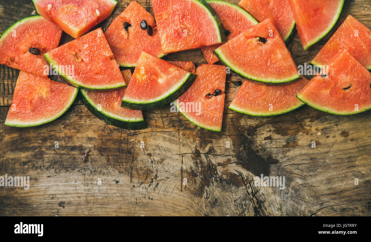Fresh summer fruit food frame. Juicy watermelon pieces over rustic wooden background, top view, copy space - Stock Image