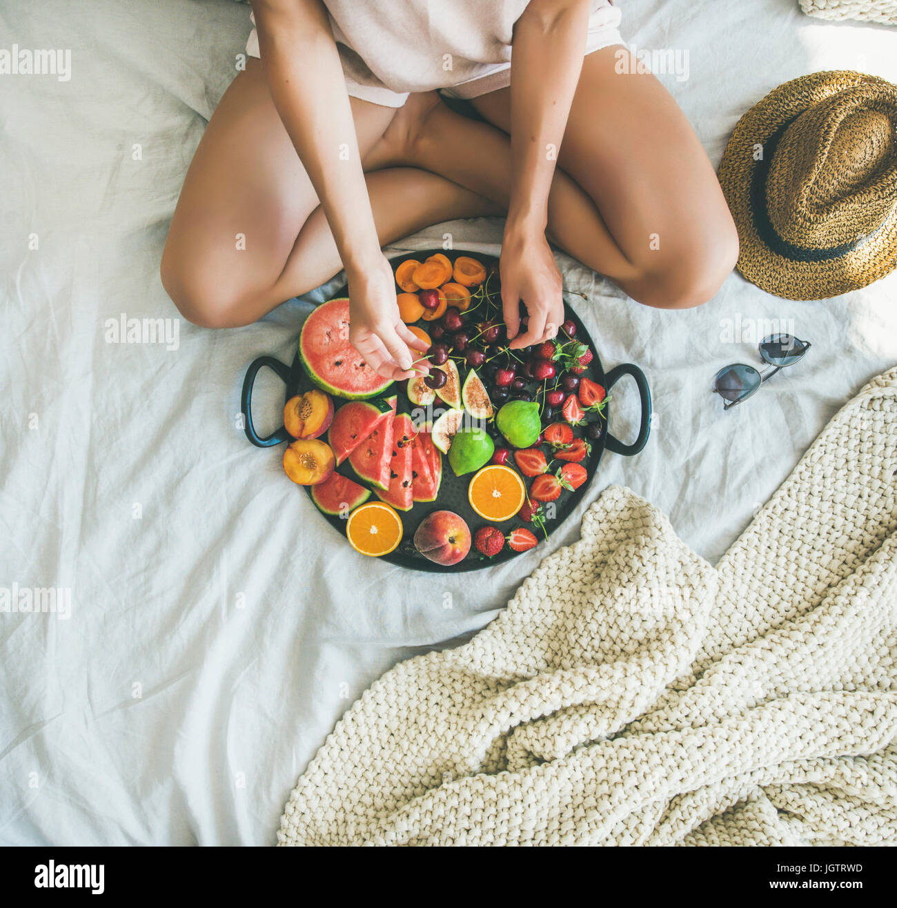 Summer healthy raw vegan clean eating breakfast in bed concept. Young girl wearing pastel colored home clothes taking - Stock Image