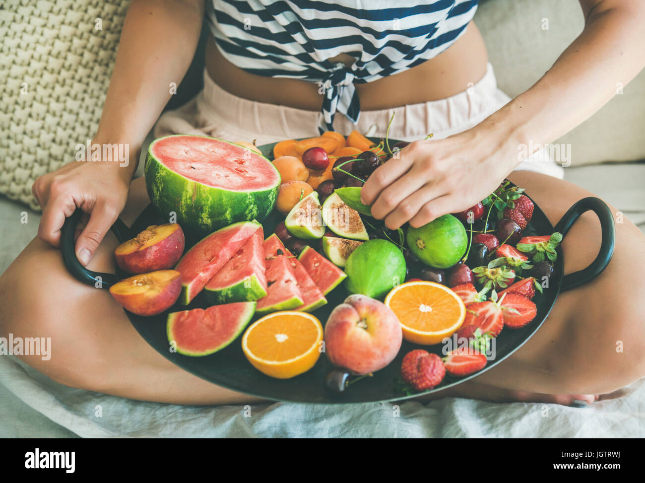 Summer healthy raw vegan clean eating breakfast in bed concept. Young girl wearing striped home shirt sitting and - Stock Image