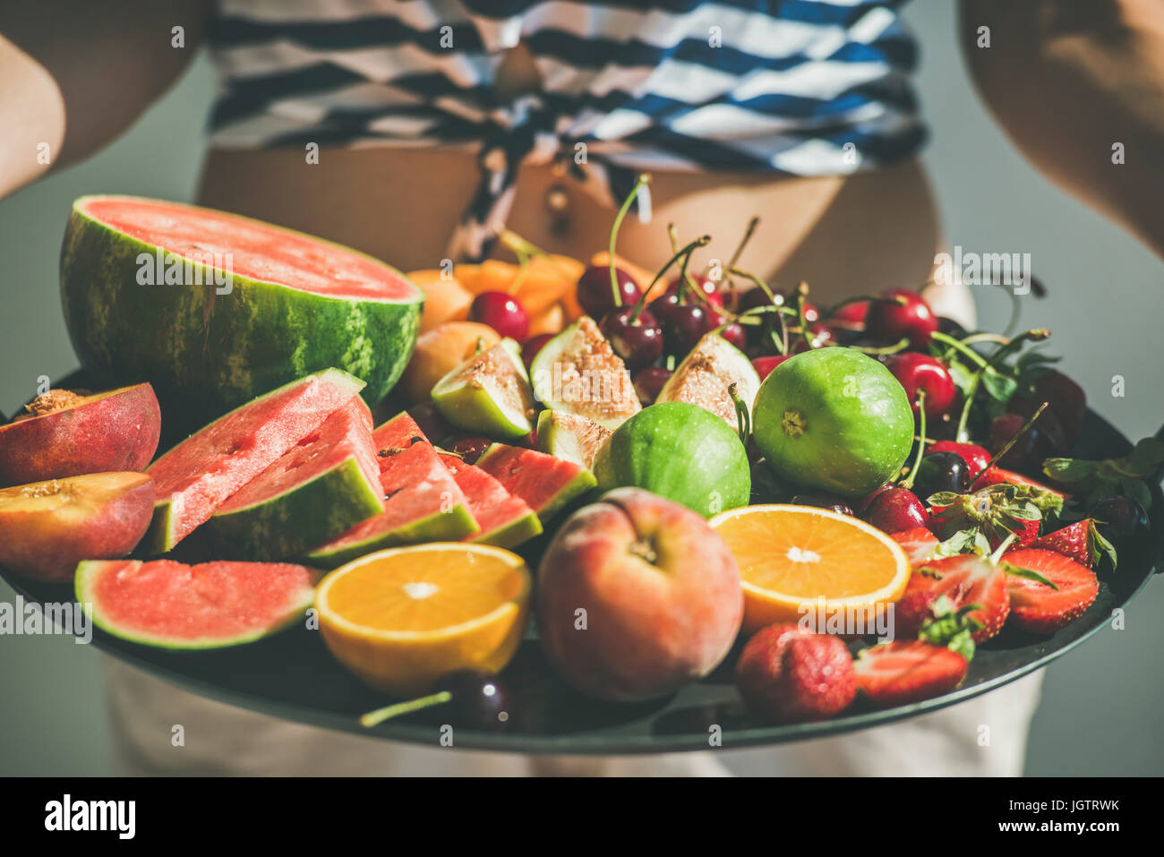 Summer healthy raw vegan clean eating breakfast in bed concept. Young girl wearing striped home shirt holding tray - Stock Image