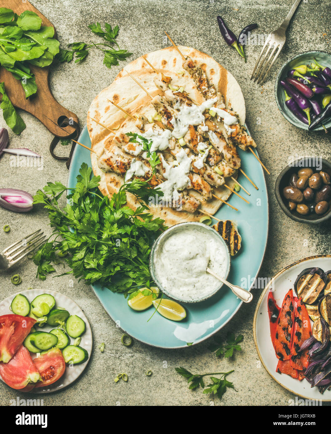 Summer barbecue party dinner set. Flatlay of grilled chicken skewers with yogurt dip, flatbreads, fresh parsley, - Stock Image