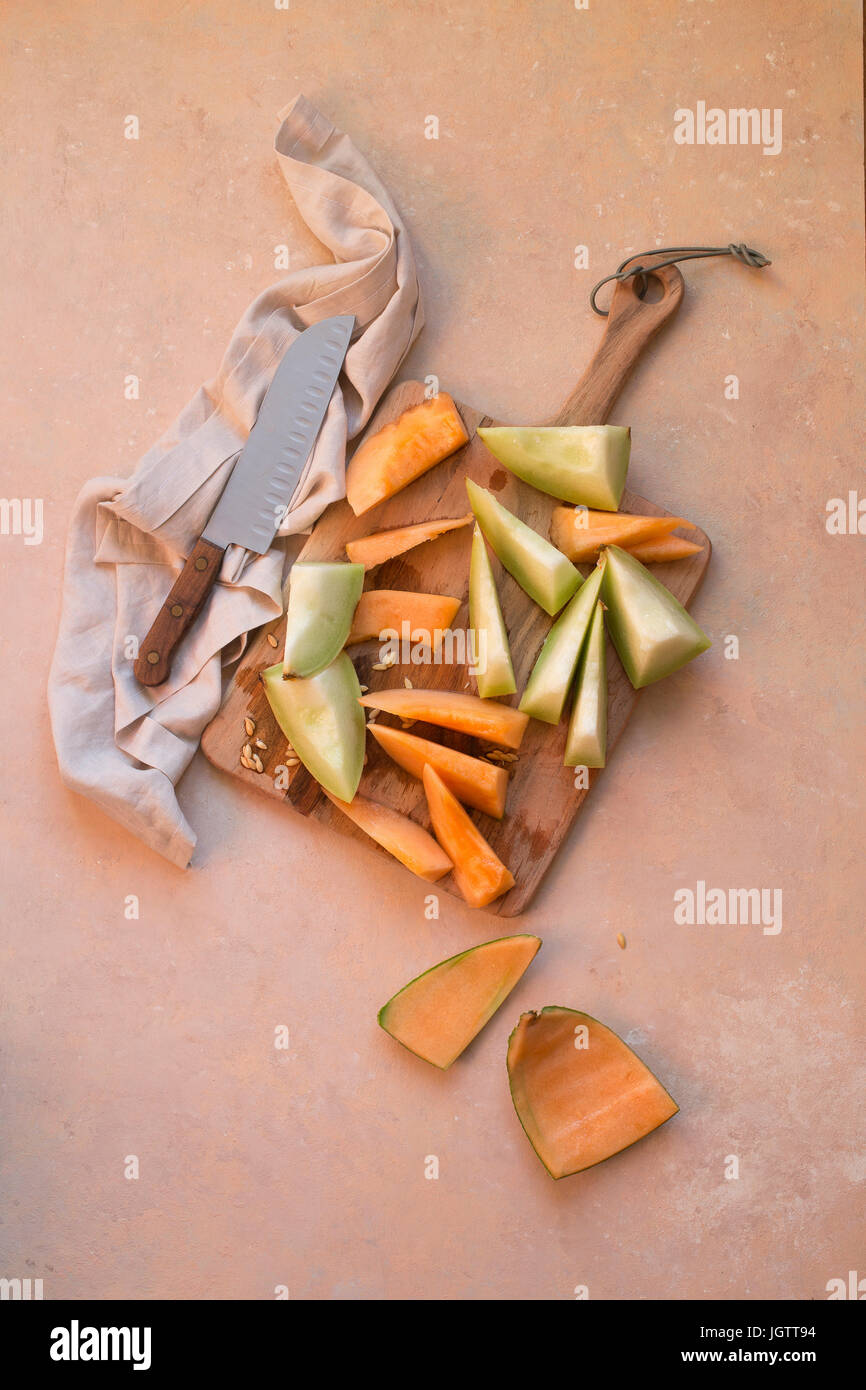 Chopped Melons on a wooden board against a peach coloured background - Stock Image