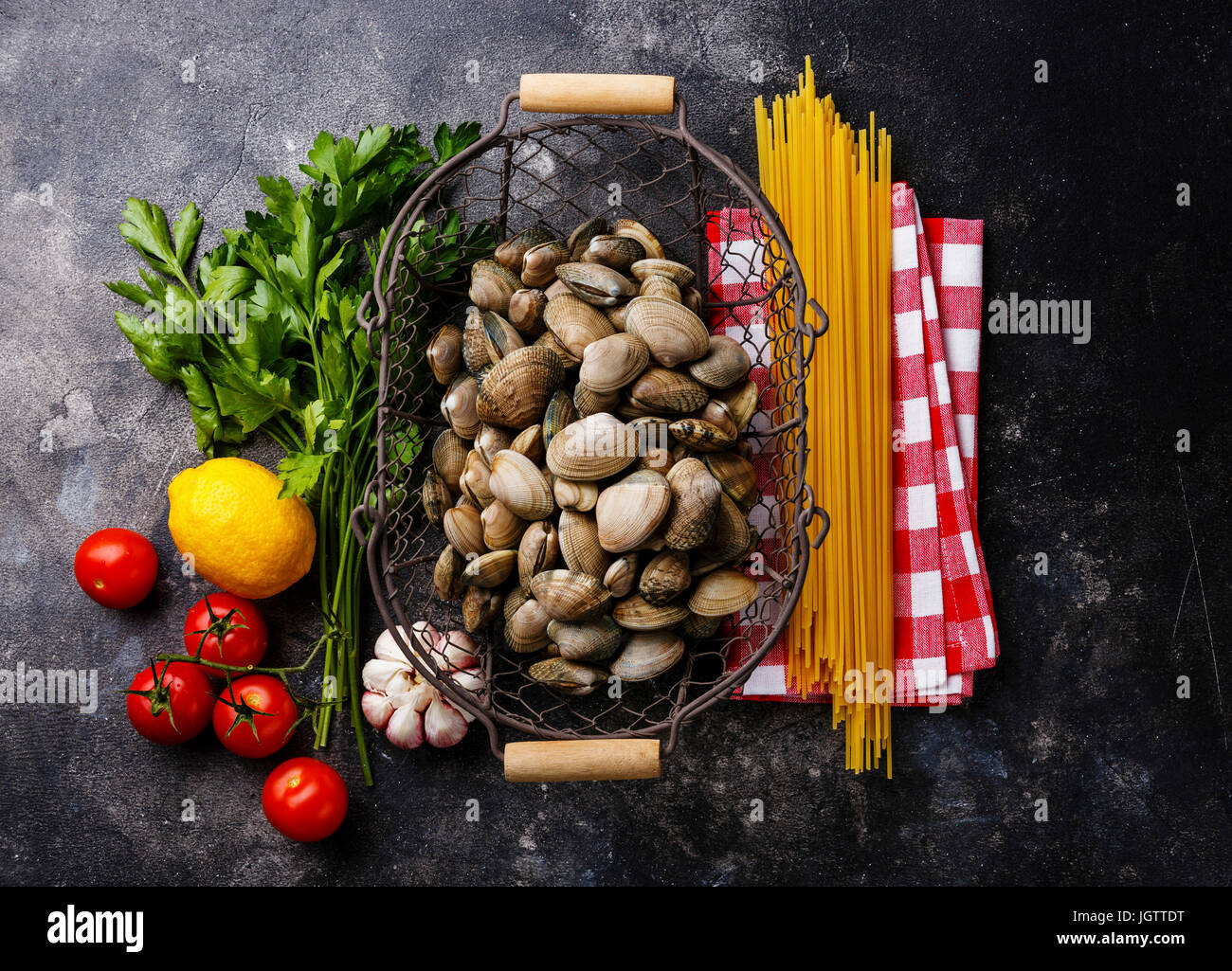 Raw food Ingredients for cooking Spaghetti alle vongole on dark background - Stock Image