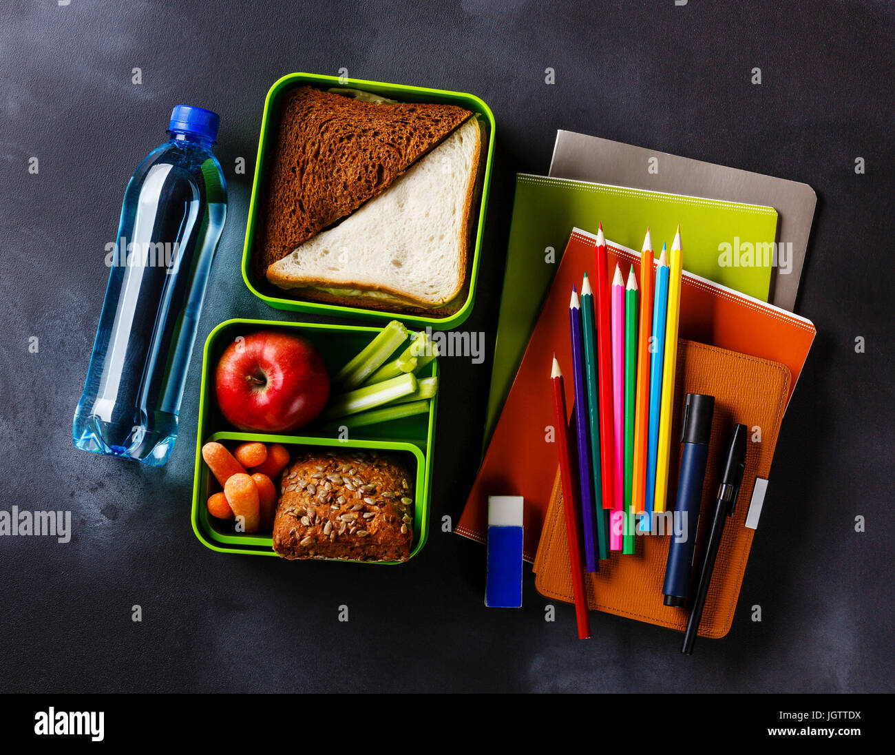 Take out food Lunch box with Sandwiches and vegetables, bottle of water and school supplies - Stock Image