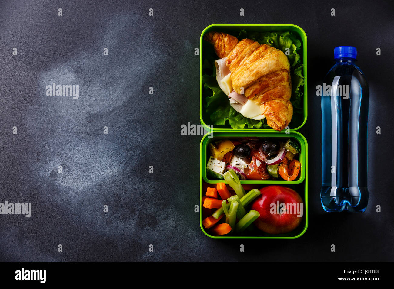 Take out food Lunch box with Croissant sandwich, Greek salad and vegetables with bottle of water on blackboard background - Stock Image