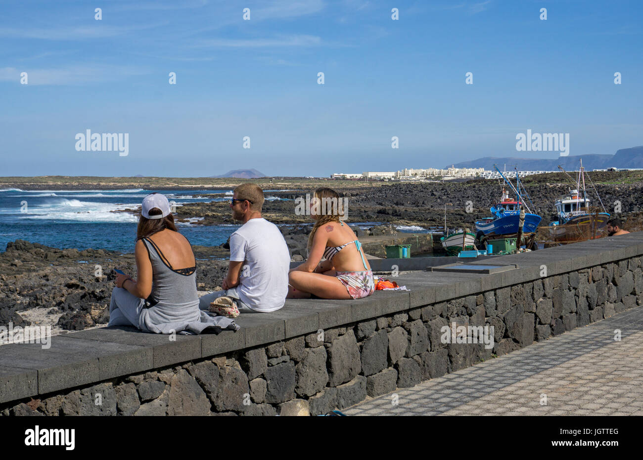 Young people sitting on harbour mural, village La Santa at north coast of Lanzarote island, Canary islands, Spain, - Stock Image