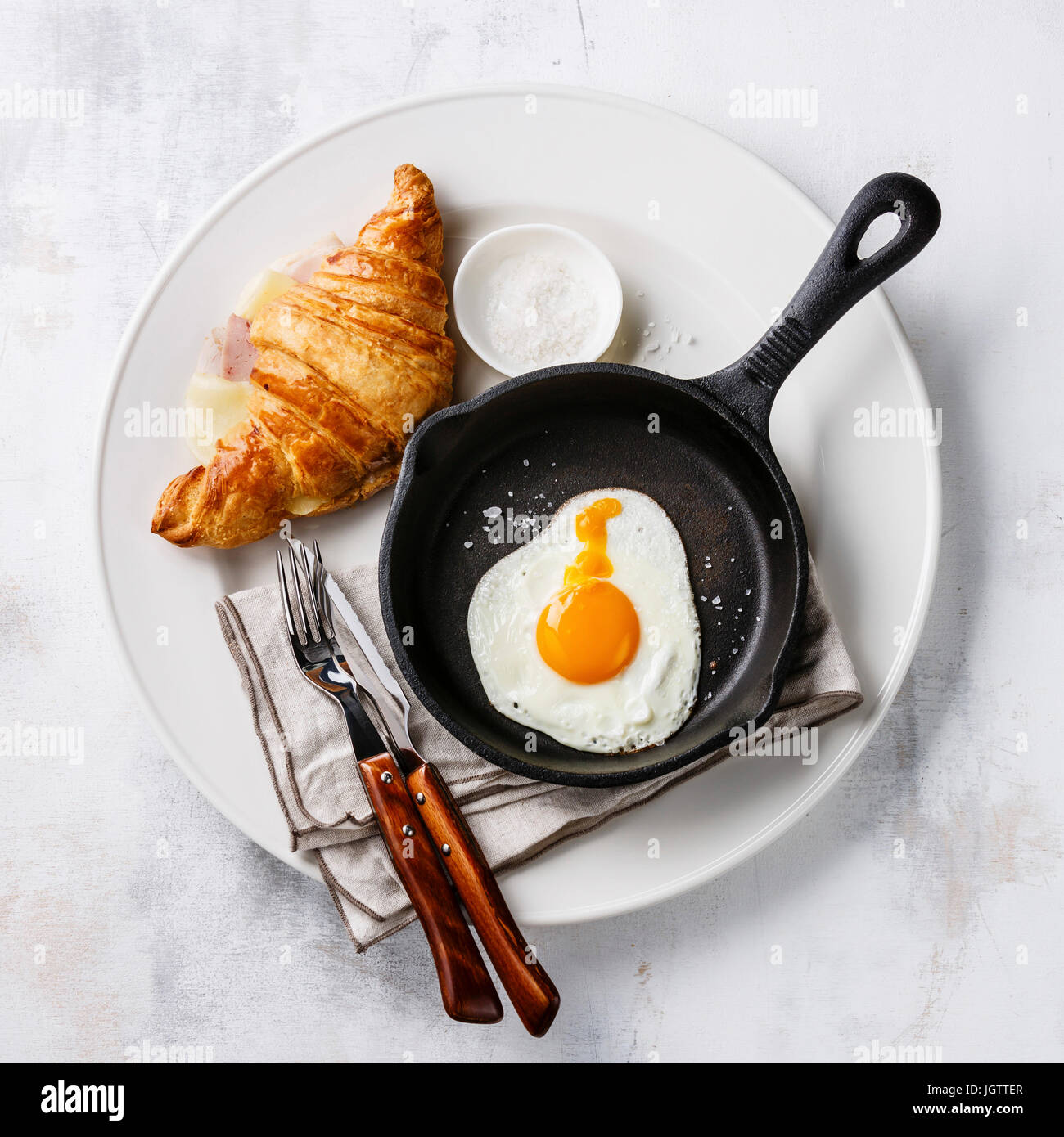 Breakfast with Fried egg on iron pan and croissant sandwich with cheese and ham on white plate on white background - Stock Image
