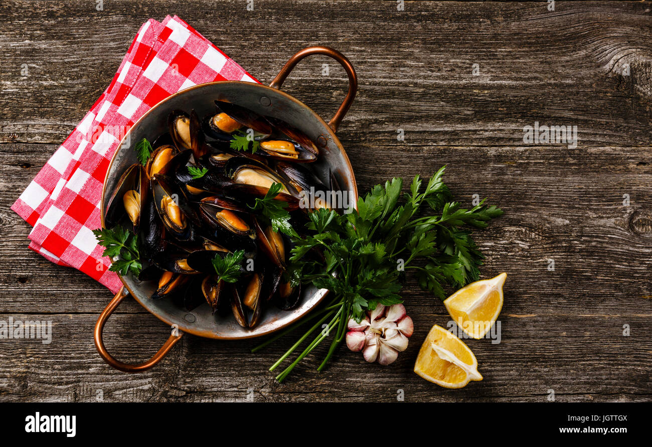 Mussels Clams in copper cooking dish pan on wooden background copy space - Stock Image