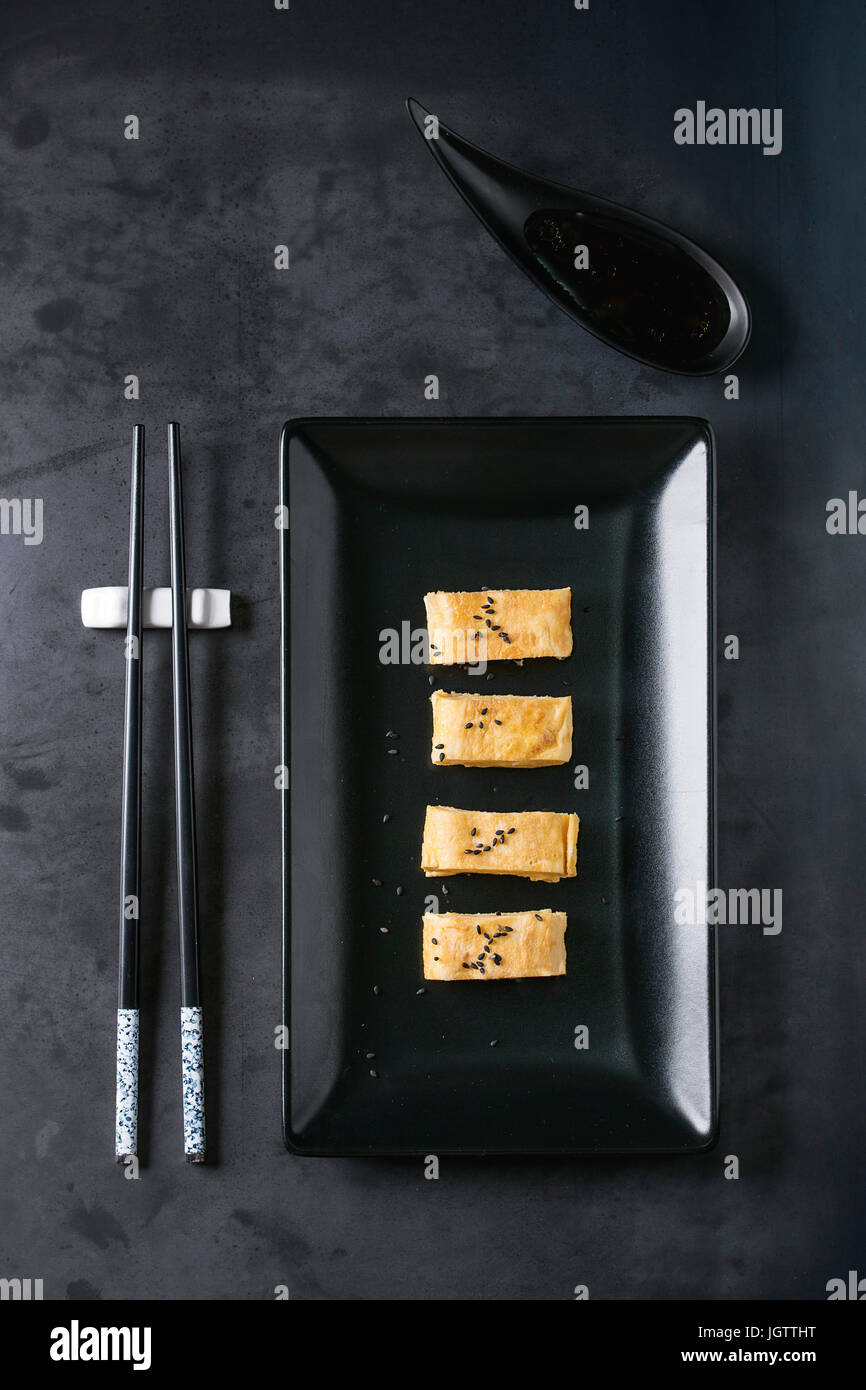 Japanese Rolled Omelet Tamagoyaki sliced with black seasame seeds and soy sauce, served in black square ceramic - Stock Image