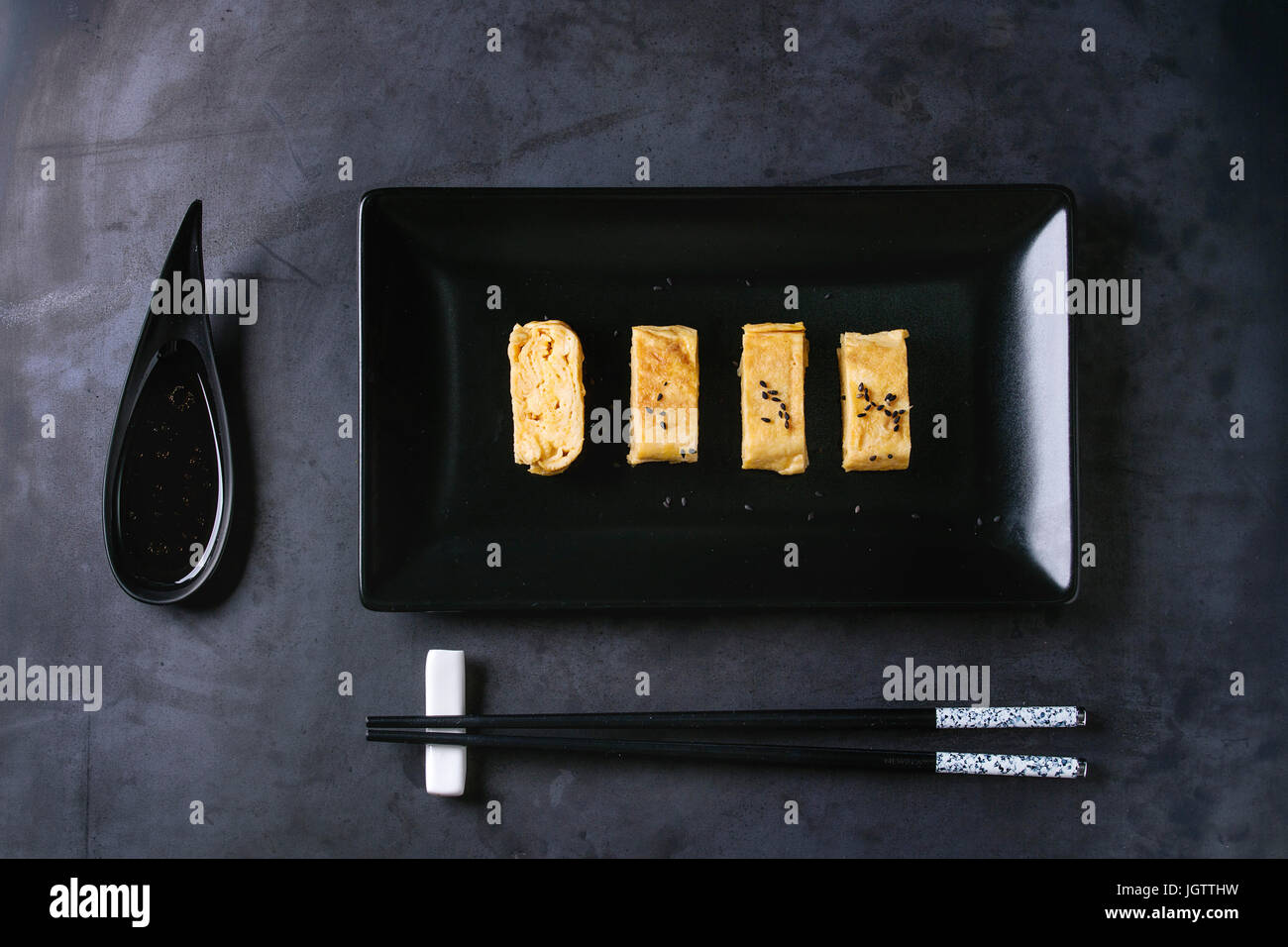 Japanese Rolled Omelette Tamagoyaki sliced with black seasame seeds and soy sauce, served in black square ceramic - Stock Image