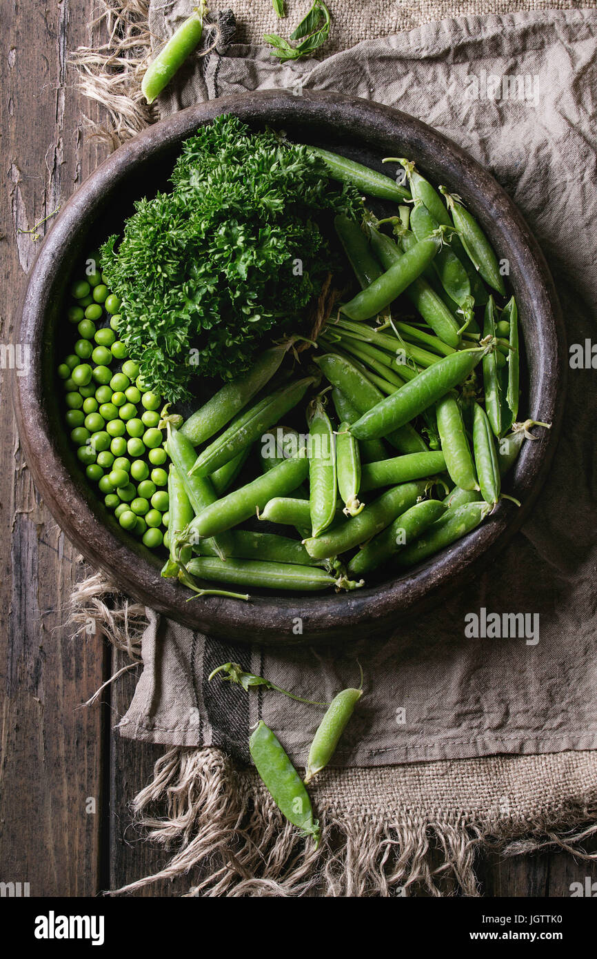 Young organic green pea pods and peas in terracotta tray and bundle of parsley over old dark wooden planks with - Stock Image