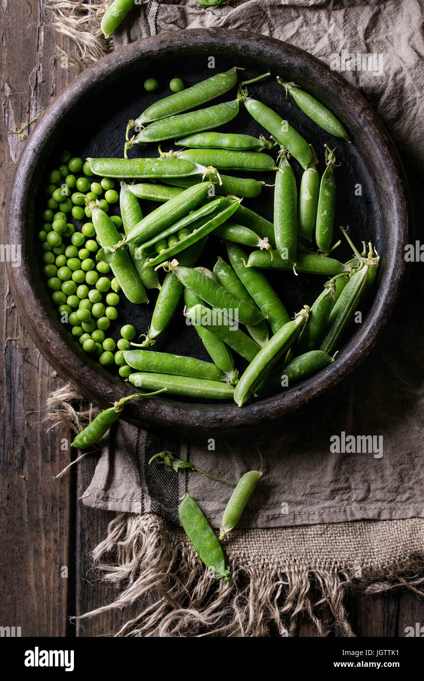 Young organic green pea pods and peas in terracotta tray over old dark wooden planks with sackcloth textile background. - Stock Image