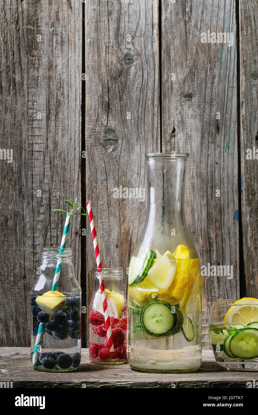 Citrus cucumber berries blueberry and rasberry sassy sassi water for detox in glass bottles with cocktail tubes - Stock Image