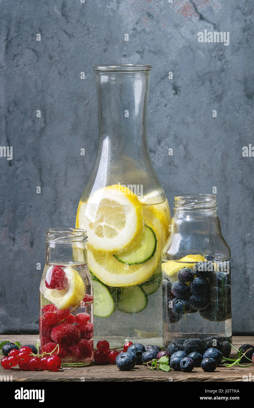 Citrus cucumber berries blueberry and rasberry sassy sassi water for detox in glass bottles on wooden blue background. - Stock Image