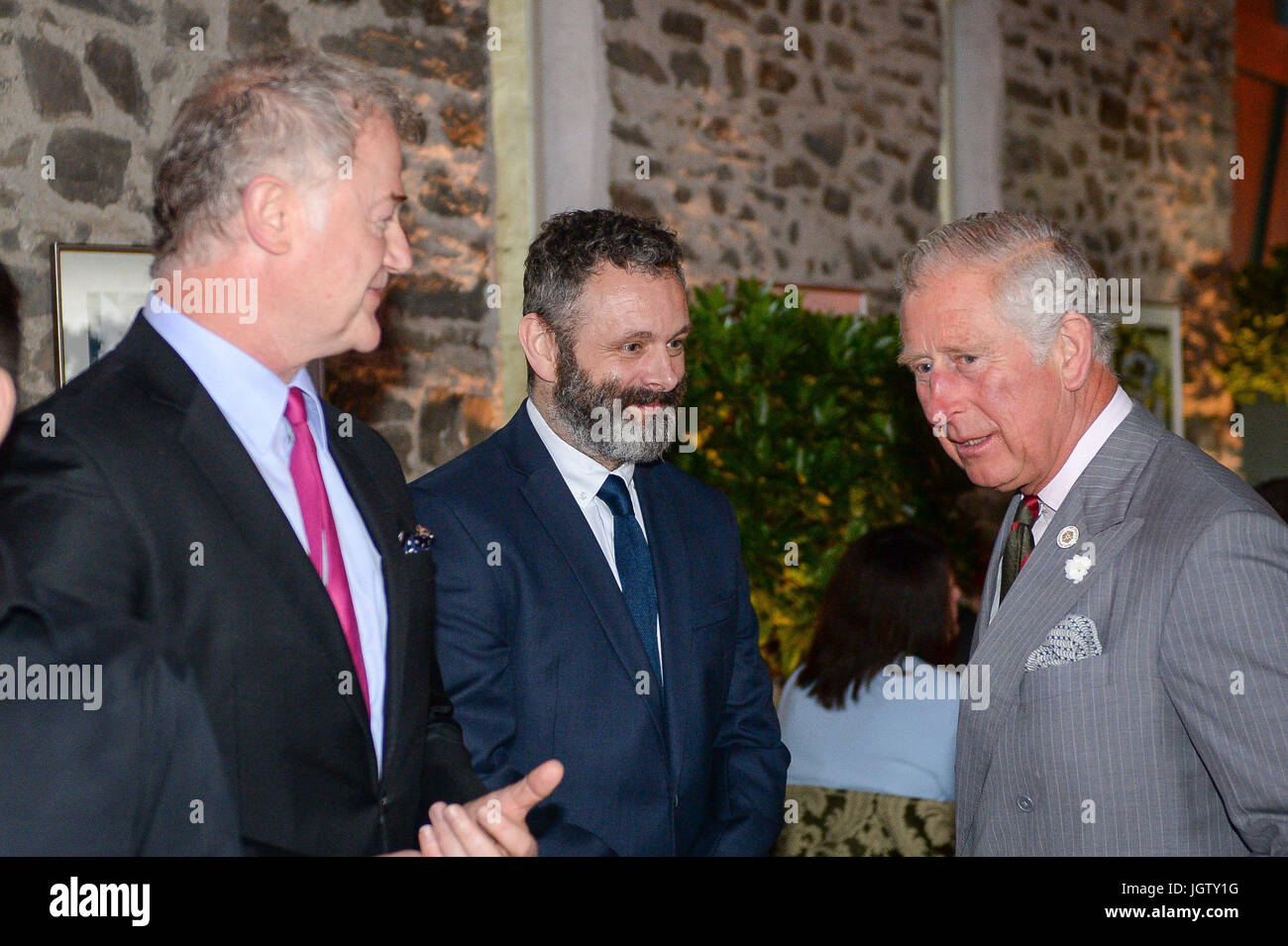 Owen Teale (left), and Michael Sheen greet the Prince of Wales at his Welsh home near Llandovery, Wales, where he - Stock Image