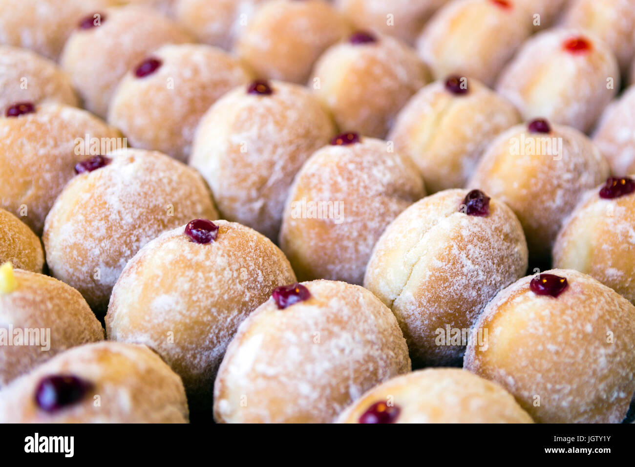 Jelly doughnuts on display in a bakery. - Stock Image