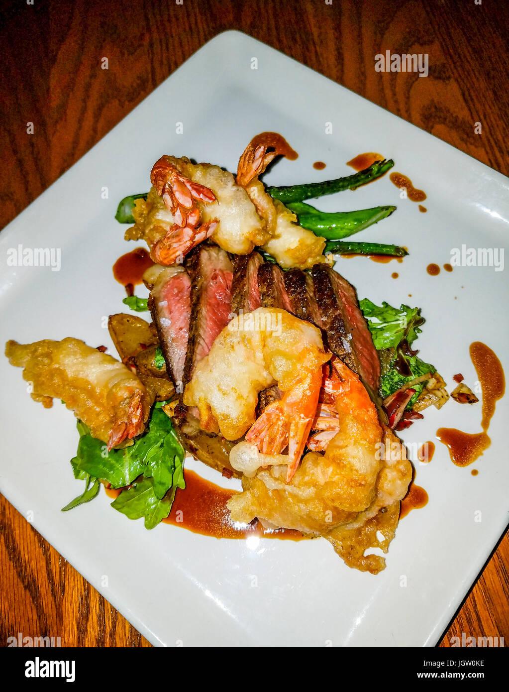 Prawn tempura over strip loin steak at Little Jumbo in Victoria, BC, Canada. - Stock Image
