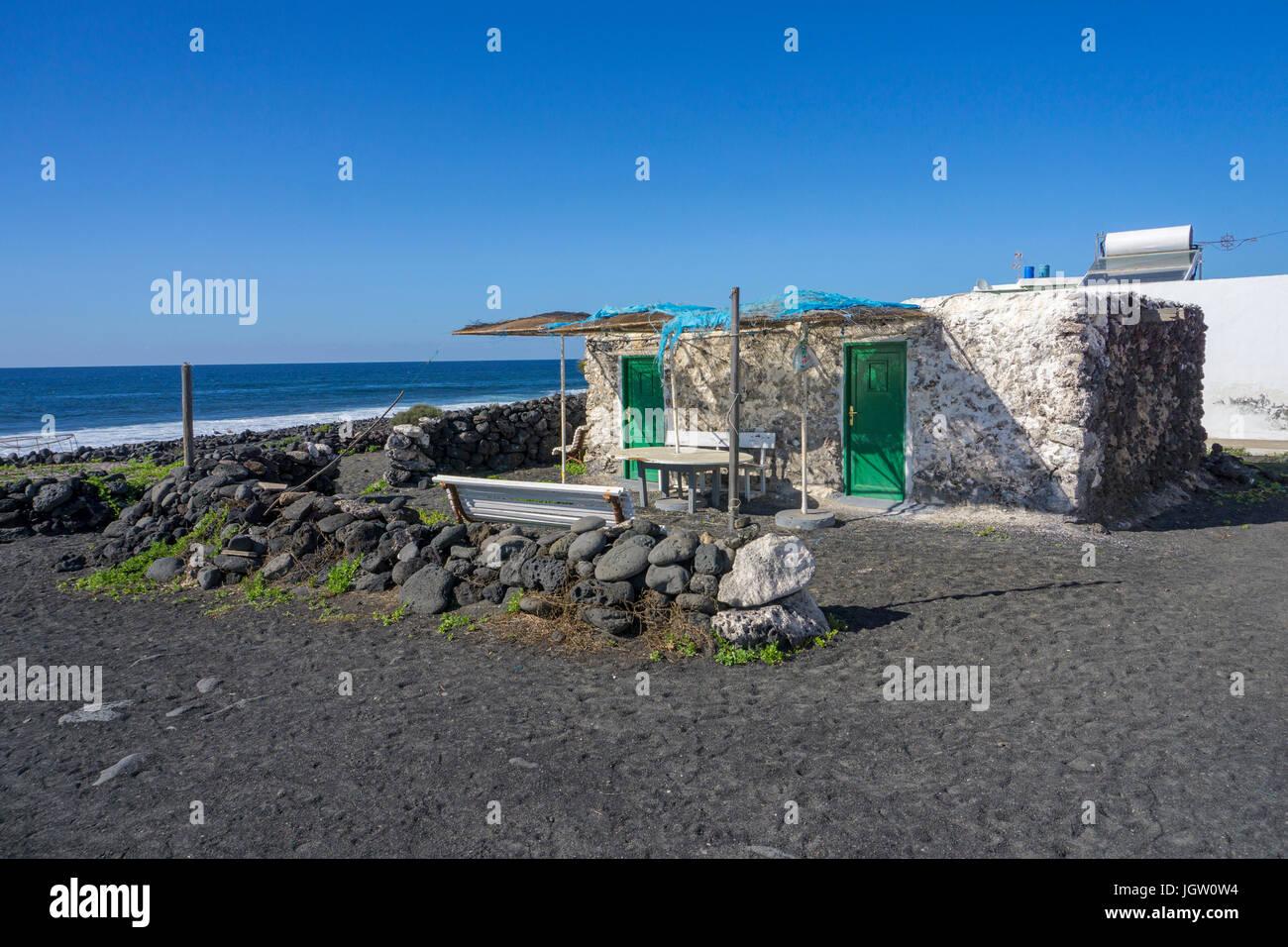 Small fishing house at the volcanic pebble beach, fishing village El Golfo, Lanzarote island, Canary islands, Spain, Stock Photo