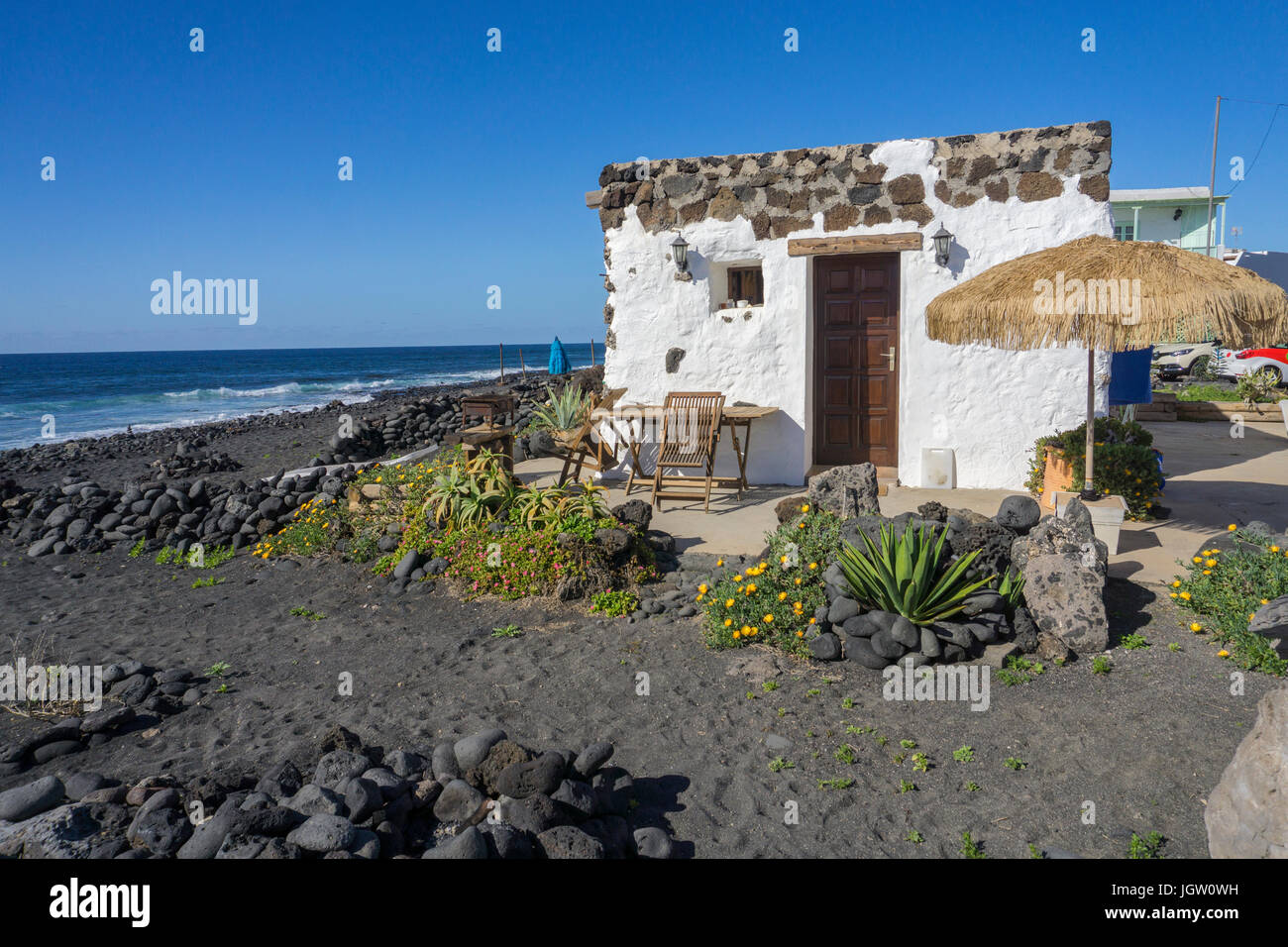 Small fishing house at the volcanic pebble beach, fishing village El Golfo, Lanzarote island, Canary islands, Spain, Stock Photo