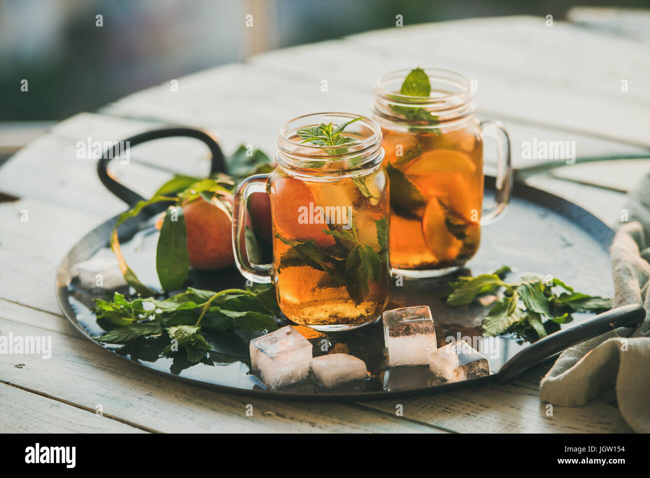 Summer refreshing cold peach ice tea on wooden table - Stock Image