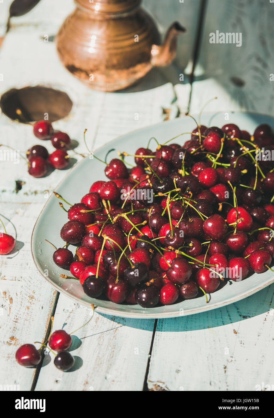 Plate of sweet cherries on light blue wooden table background - Stock Image