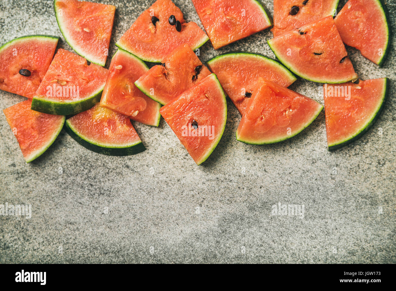 Juicy watermelon pieces over concrete stone background - Stock Image