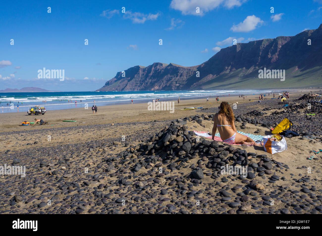 Girl takes a sunbath at Famara beach, Famara mountains, La Caleta de Famara, Lanzarote island, Canary islands, Spain, - Stock Image